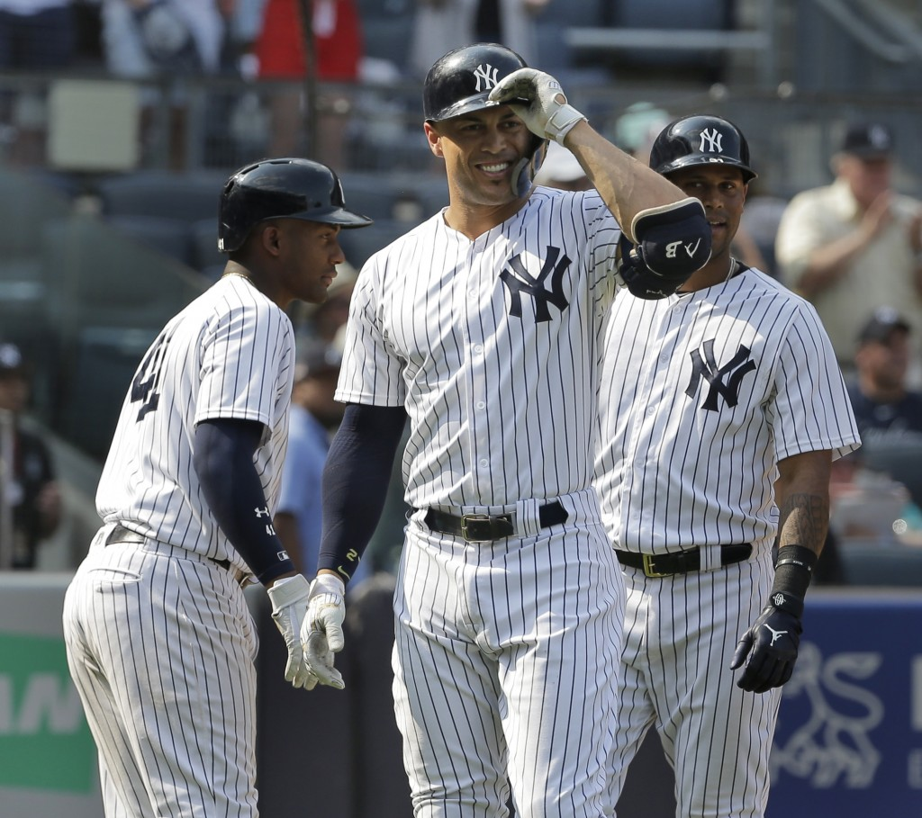 New York Yankees' Giancarlo Stanton, center, reacts after believing he hit a home run during the eighth inning of a baseball game against the Tampa Ba...