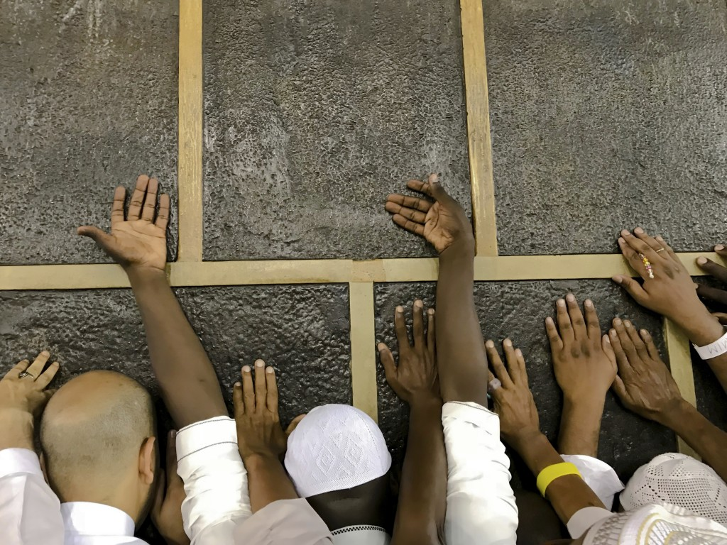 Muslim pilgrims touch the Kaaba stone, the cubic building at the Grand Mosque, as they pray ahead of the annual Hajj pilgrimage in the Muslim holy cit...