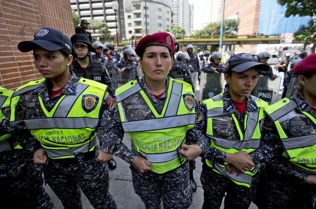 Venezuelan Bolivarian national police officers make a barrier to block a group of nurses and employees of public hospitals from marching towards Miraf...