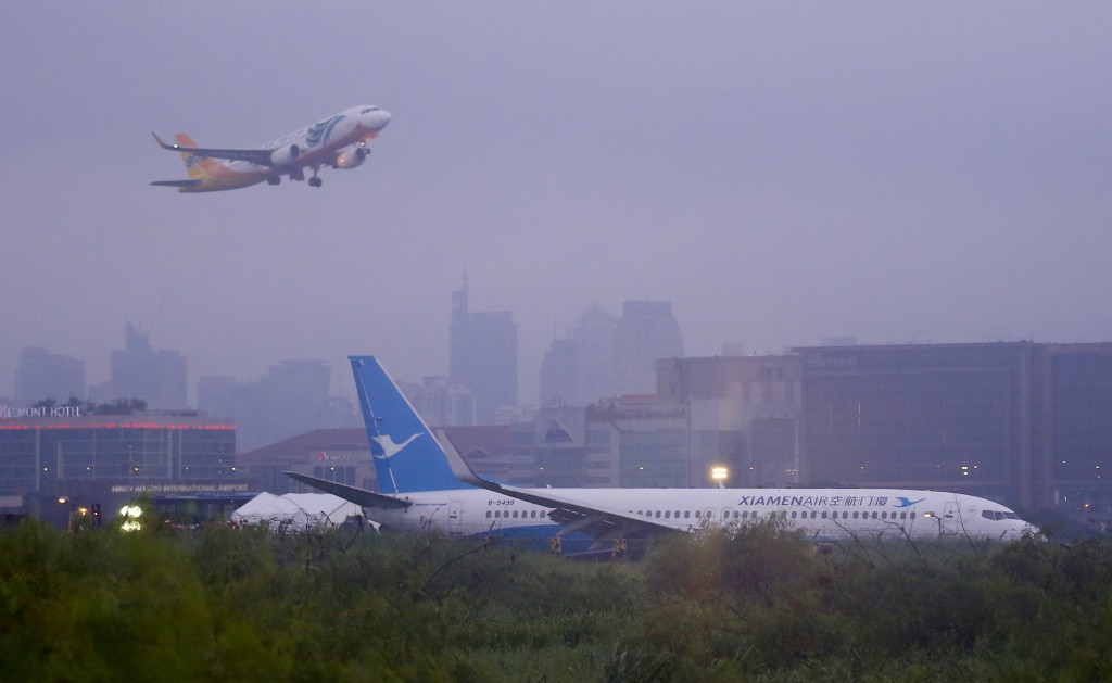 A Cebu Pacific passenger plane takes off, in background, while a Boeing passenger plane from China, a Xiamen Air, lies on the grassy portion of the ru...