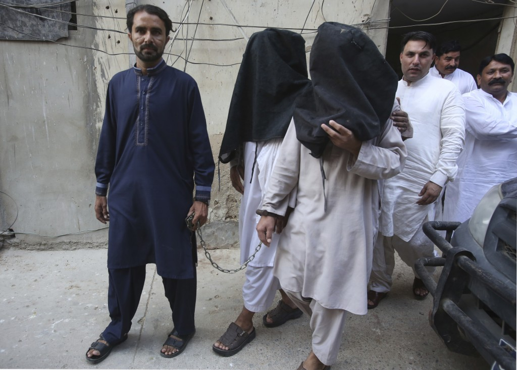 FILE - In this Aug. 10, 2018 file photo, a security official escorts family members of suicide bomber Hafeez Nawaz, with their faces covered for inter...