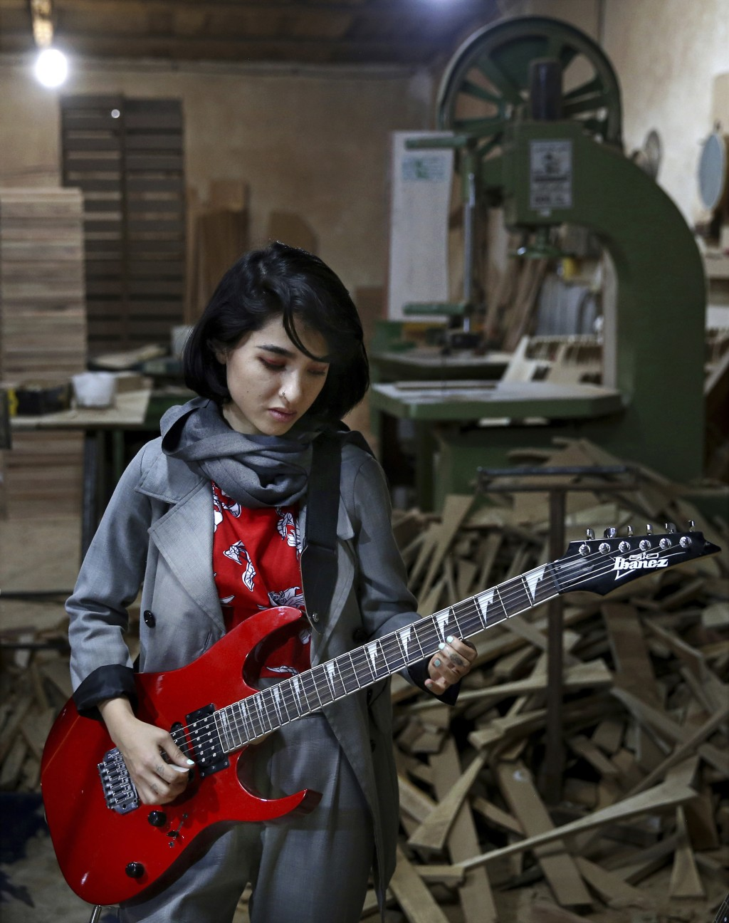 In this July 20, 2018 photo, Afghan musician Soraya Hosseini, a member of the Arikayn rock band, plays guitar at a furniture workshop in Eslamshahr, o...