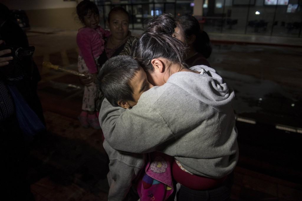 In this Aug. 14, 2018 photo, Anthony David Tovar Ortiz, left, is embraced by a relative after arriving to La Aurora airport in Guatemala City. The 8-y...