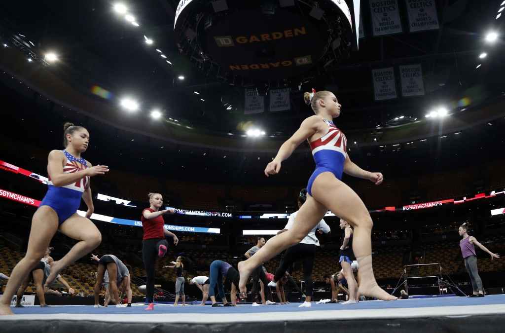 FILE - In this Aug. 15, 2018, file photo, Ragan Smith, right, warms up with other athletes during a training session at the U.S. Gymnastics Championsh...
