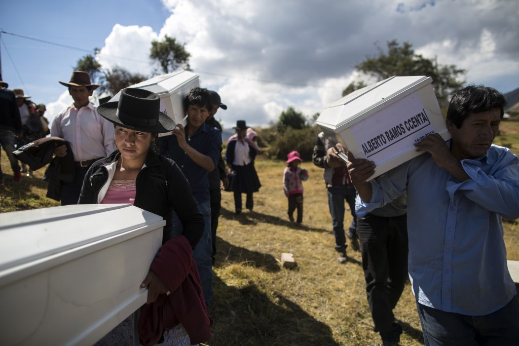 In this Aug. 15, 2018 photo, the relatives of people who were killed by the Shining Path guerrillas and the Peruvian army in the 1980s carry their rem...