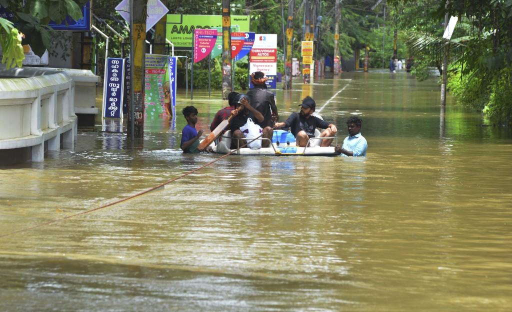 People move past a flooded area in Thrissur, in the southern Indian state of Kerala, Friday, Aug. 17, 2018. Rescuers used helicopters and boats on Fri...
