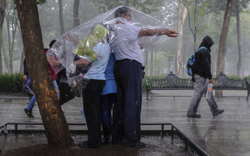 In this Aug. 12, 2018 photo, Fernando Rodriguez Garcia covers his family with a plastic sheet during a sudden downpour as he and his family take a wal...