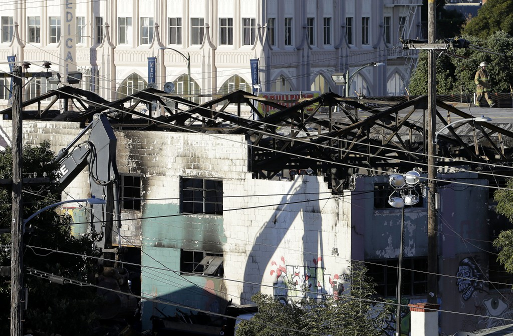 FILE - In this Dec. 6, 2016 file photo, an emergency crew worker, top right, walks on a roof next to the site of a warehouse fire in Oakland, Calif. A...
