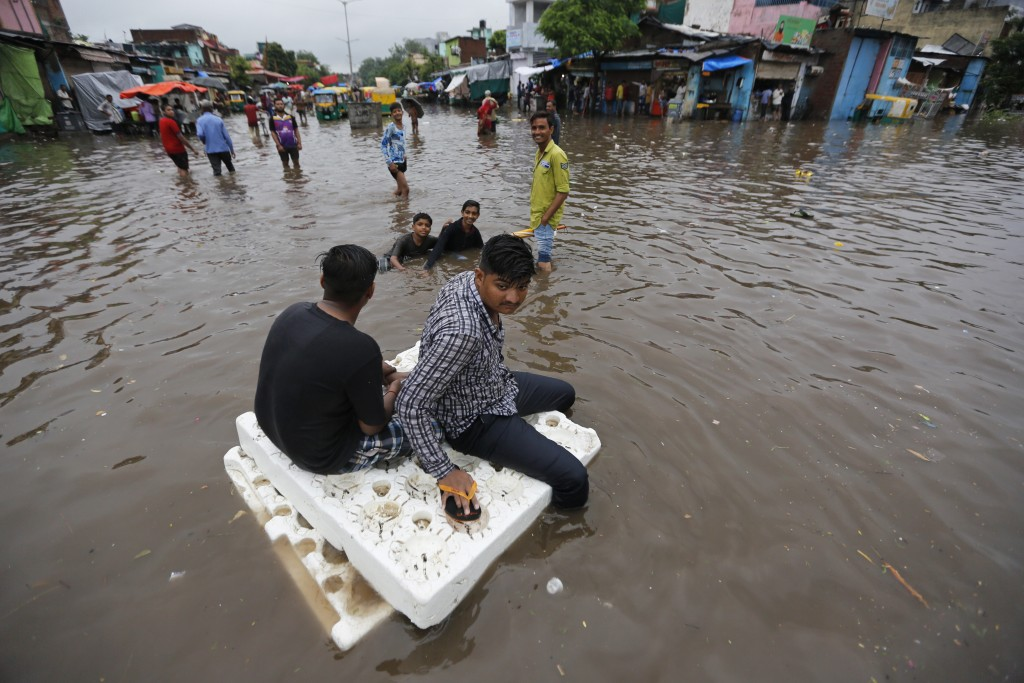 Indian men use thermocol sheets as a makeshift raft on a flooded road after heavy rainfall in Ahmadabad, India, Friday, Aug. 17, 2018. India receives ...