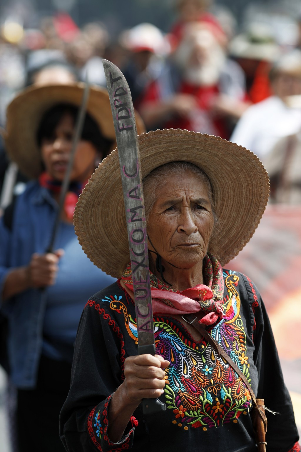 In this Aug. 14, 2018 photo, a woman holds a up machete during a march to the headquarters of Mexico's President-elect Andres Manuel Lopez Obrador to ...