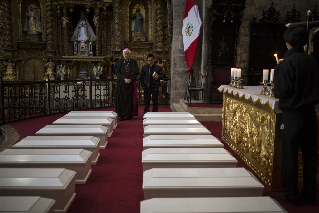 In this Aug. 14, 2018 photo, Ayacucho's Bishop Salvador Jose Miguel Pineiro, left, stands with an assistant behind the coffins of villagers who were k...