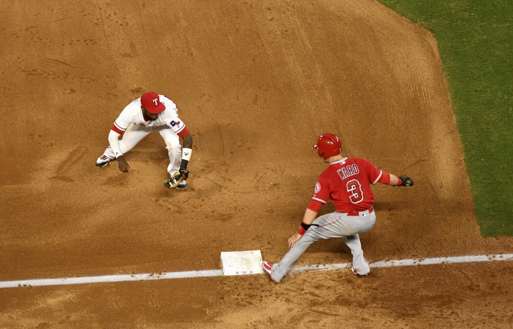 Texas Rangers shortstop Jurickson Profar runs to tag out Los Angeles Angels' Taylor Ward (3) for one out of a triple play on a ground ball by David Fl...