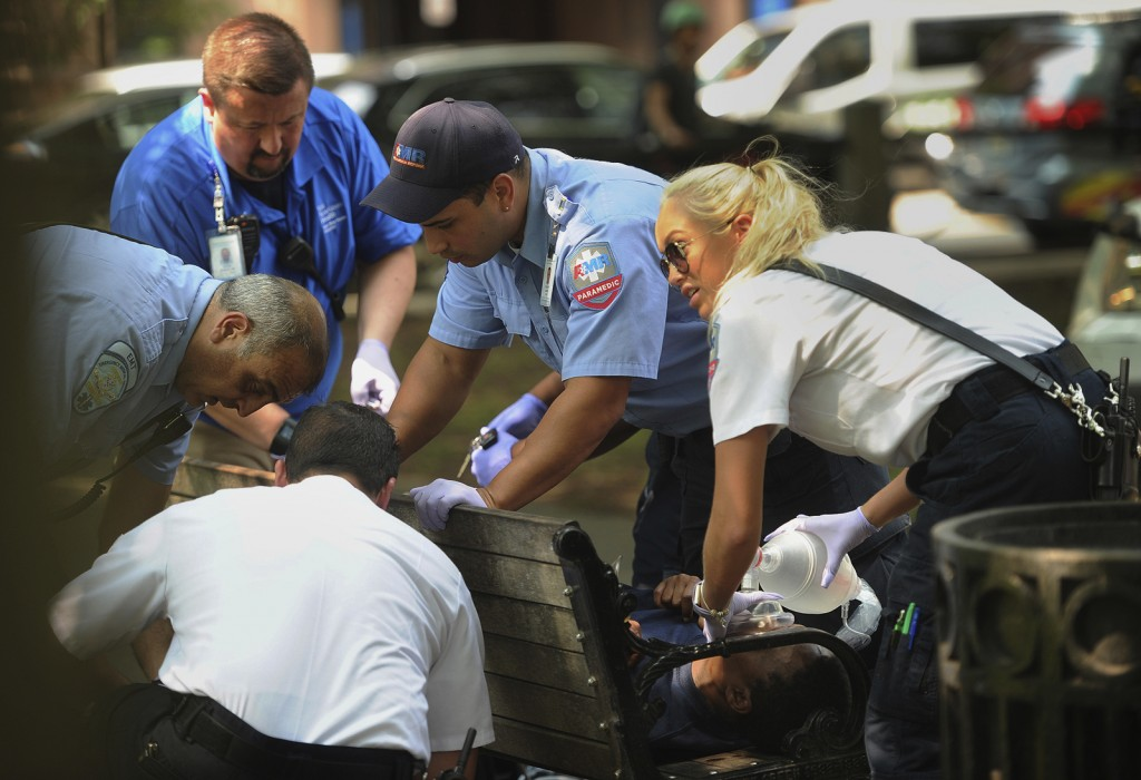 FILE - In this Thursday, Aug. 16, 2018 file photo, paramedics and EMT members respond to one of three simultaneous drug overdose victims on the New Ha...