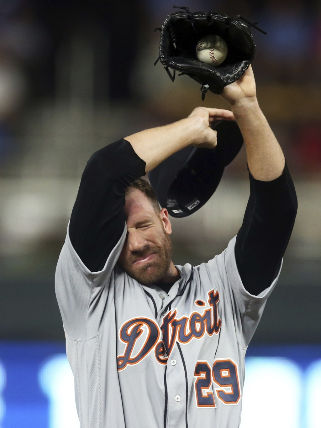 Detroit Tigers pitcher Zach McAllister wipes his face after giving up a hit to Minnesota Twins' Logan Forsythe during the sixth inning of a baseball g...