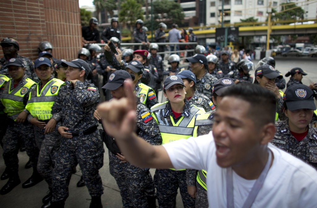 A line of police officers stand blocking a street, stoping a protests against the government of President Nicolas Maduro, in Caracas, Venezuela, Thurs...