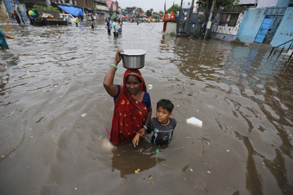 An Indian woman and a child wade past floodwaters after heavy rainfall in Ahmadabad, India, Friday, Aug. 17, 2018. India receives its annual rainfall ...