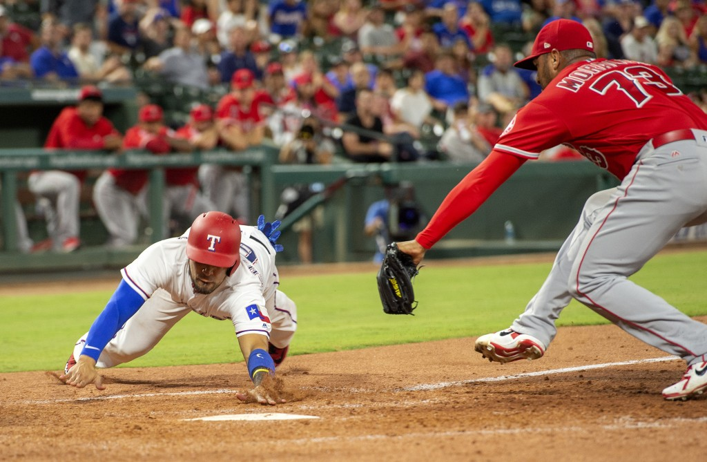 Texas Rangers' Robinson Chirinos scores ahead of the tag of Los Angeles Angels relief pitcher Osmer Morales (73) on a wild pitch by Morales during the...