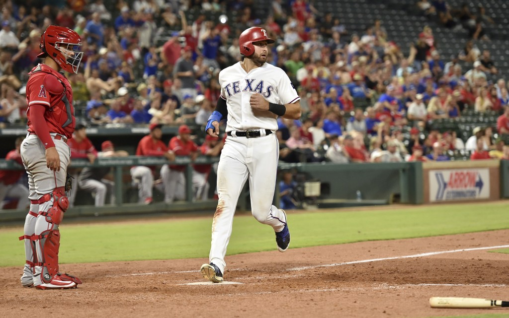 Texas Rangers' Joey Gallo scores the go-ahead run on an infield single by Rougned Odor off Los Angeles Angels relief pitcher Justin Anderson, while ca...