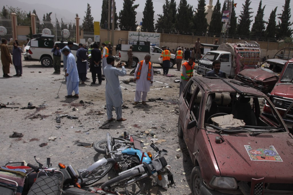 FILE - In this July 25, 2018, file photo, Pakistani security officials visit the site of a suicide bombing which killed dozens of people as Pakistanis...