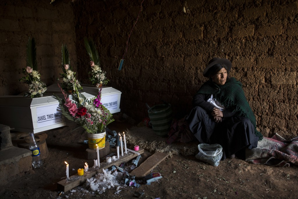 In this Aug. 15, 2018 photo, Marta Tineo Espinosa sits next to the coffins of her relatives who were killed by the Shining Path guerrillas and the Per...