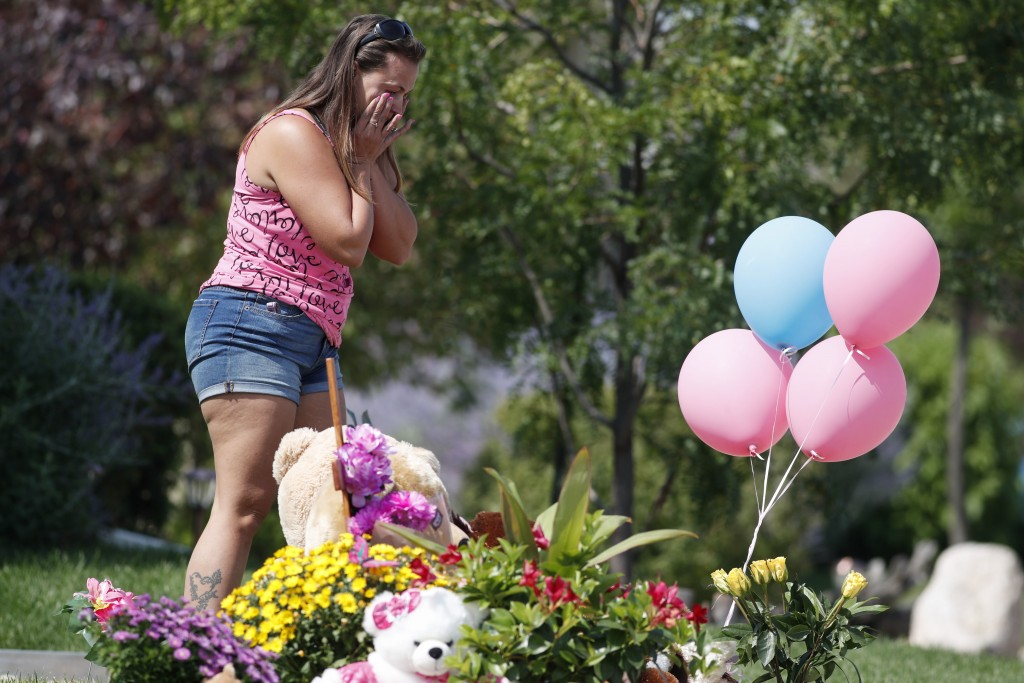 Ashley Bell reacts after leaving flowers among the tributes growing outside the home where a pregnant woman and her two daughters lived Thursday, Aug....