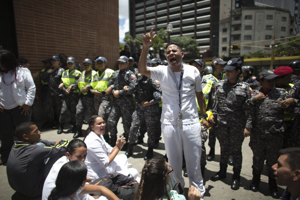 Nurses shout anti-government slogans as they are confronted by a line of police officers during a protests against the government of President Nicolas...