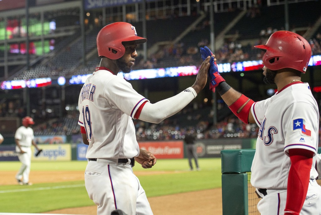 Texas Rangers' Jurickson Profar, front left, is congratulated by Elvis Andrus after scoring on a bases-loaded walk of Shin-Soo Choo by Los Angeles Ang...