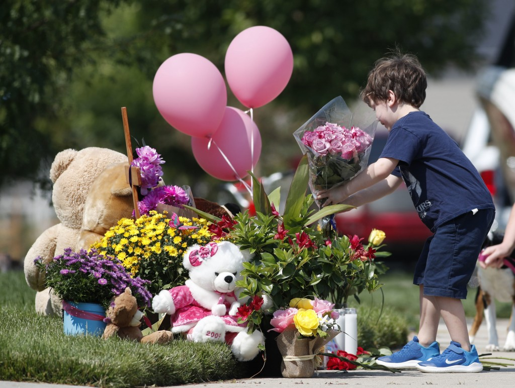 An unidentified young boy places a bouquet of flowers on a pile of tributes outside the home where a pregnant woman and her two daughters lived Thursd...