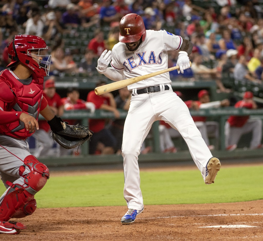 Texas Rangers' Delino DeShields reacts to being hit by a pitch from Los Angeles Angels relief pitcher Ty Buttrey, next to catcher Francisco Arcia duri...