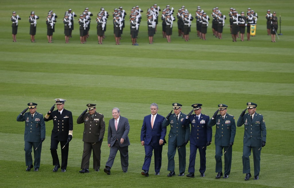In this Aug. 14, 2018 photo, Colombia's President Ivan Duque, fifth from left, walks with his new Defense Minister Guillermo Botero, fourth from left,...