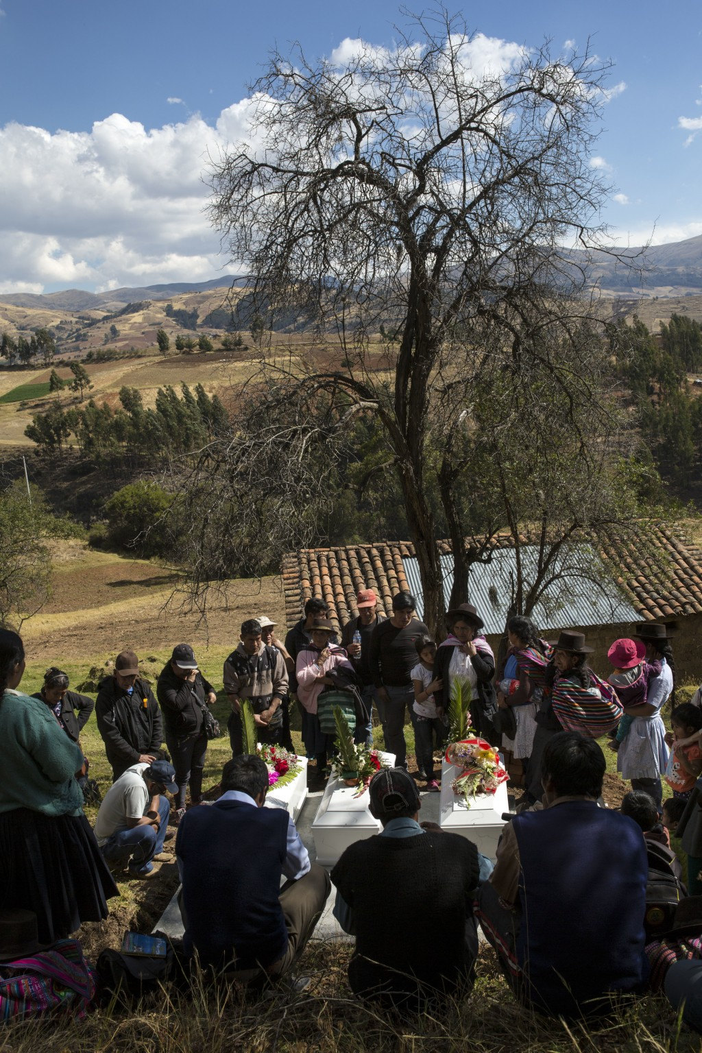 In this Aug. 15, 2018 photo, villagers gather around the coffins of their loved ones who were killed by Shining Path guerrillas in 1984, during their ...