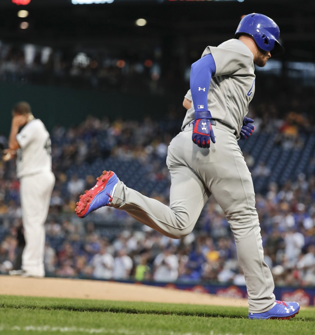 Chicago Cubs' Ian Happ rounds the bases after hitting a solo home run off Pittsburgh Pirates starting pitcher Ivan Nova, left, during the fourth innin...