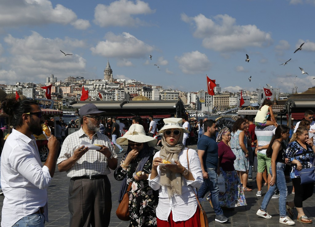 Tourists walk by the Golden Horn in Istanbul, Thursday, Aug. 16, 2018. Beset by a weak currency and tension with the United States, Turkey is reaching...