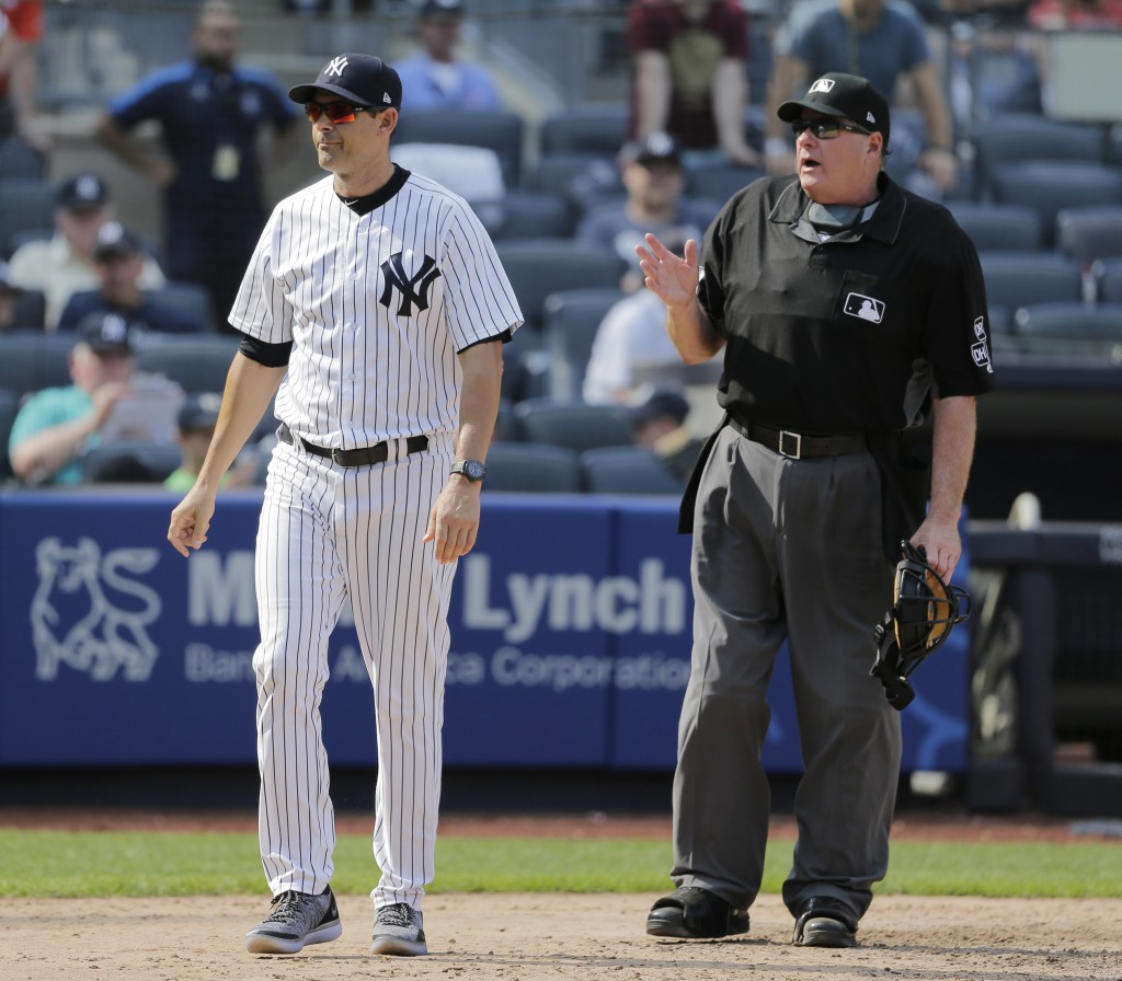 New York Yankees manager Aaron Boone, left, argues with umpire Jerry Layne after the umpires ruled a hit by Giancarlo Stanton a ground rule double dur...