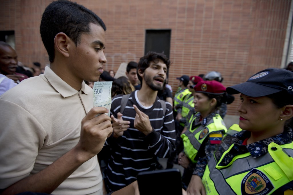 A demonstrator shows a bank note of five hundred Bolivars to a line of police officers during protest in Caracas, Venezuela, Thursday, Aug. 16, 2018. ...