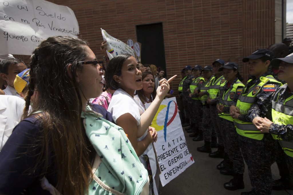 Nurses are confronted by a line of police officers during a protests against the government of President Nicolas Maduro, in Caracas, Venezuela, Thursd...