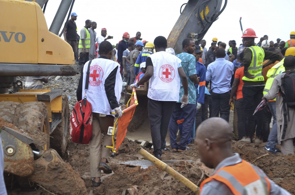 Rescue workers search for trapped people under the rubble of a collapsed under construction building in Abuja Nigeria, Friday, Aug. 17, 2018. Nigerian...