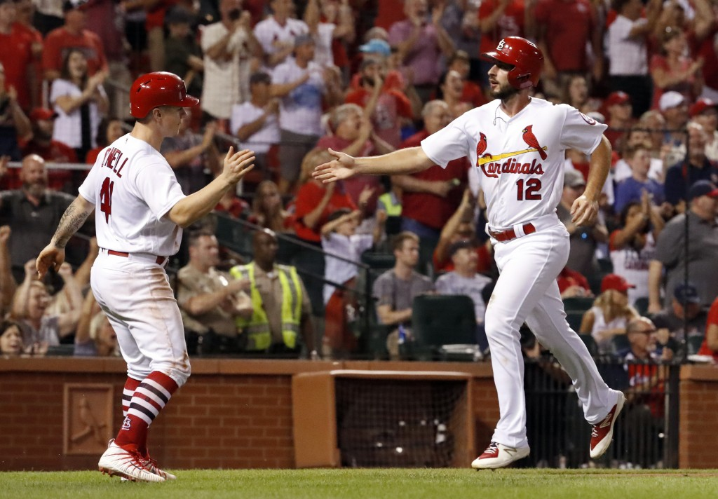 St. Louis Cardinals' Paul DeJong (12) and Tyler O'Neill celebrate after scoring on a double by Kolten Wong during the eighth inning of a baseball game...