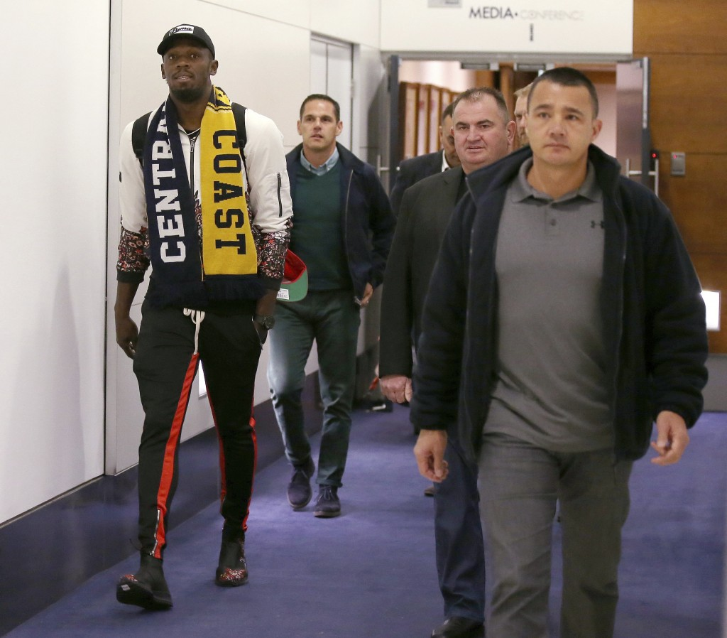 Jamaica's Usain Bolt, left, arrives in Sydney, Saturday, Aug. 18, 2018.  Olympic gold medalist, Bolt is hoping to impress the coaching staff enough to...