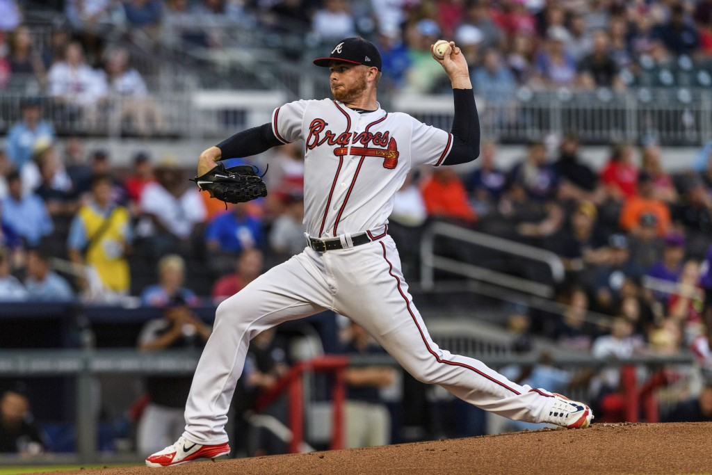 Atlanta Braves starting pitcher Sean Newcomb works against the Colorado Rockies in the first inning of a baseball game in Atlanta, Friday, Aug. 17, 20...