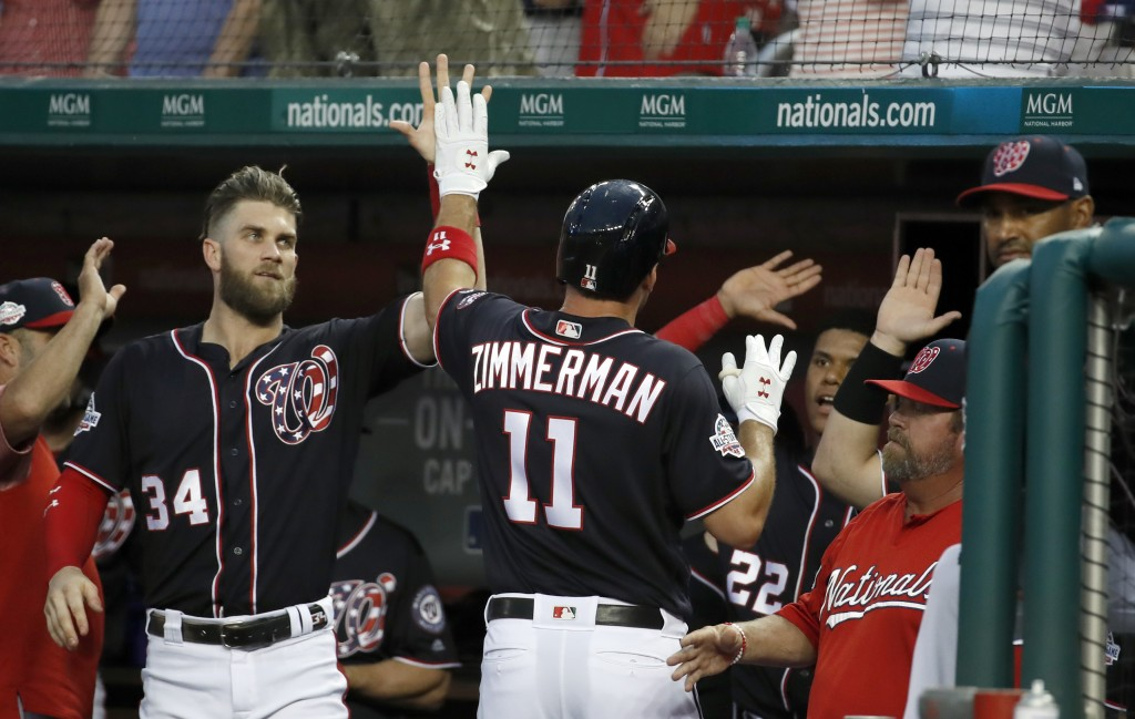 Washington Nationals' Ryan Zimmerman celebrates his solo home run with Bryce Harper (34) and others during the second inning of a baseball game agains...