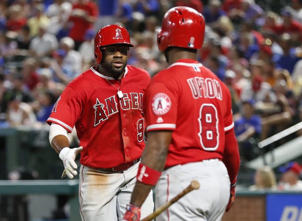Los Angeles Angels' Eric Young Jr. (9) is congratulated by Justin Upton (8) after scoring on a single by David Fletcher against the Texas Rangers duri...