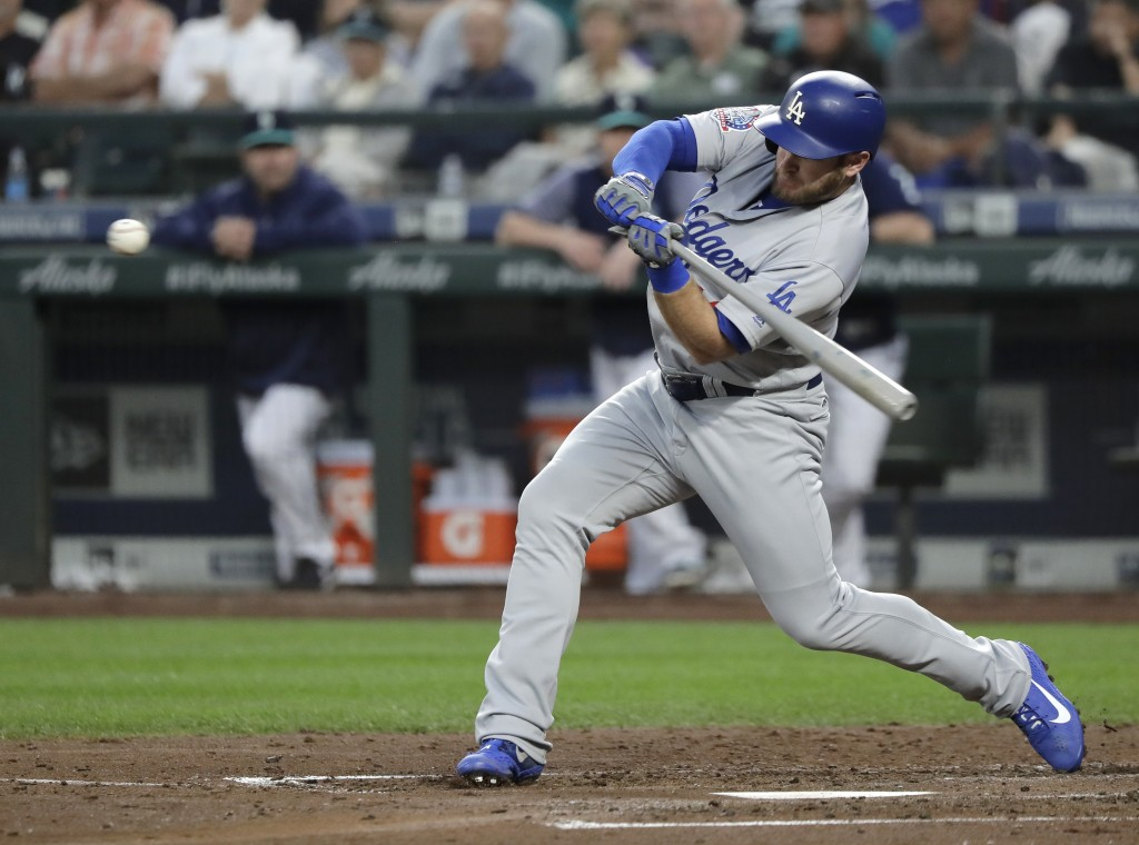 Los Angeles Dodgers' Max Muncy begins his swing on a two-run home run during the fourth inning of a baseball game against the Seattle Mariners, Friday...