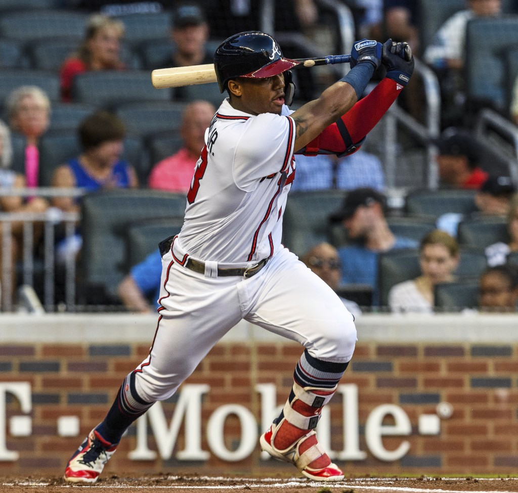 Atlanta Braves' Ronald Acuna Jr. hits a single in the first inning of a baseball game against the Colorado Rockies in Atlanta, Friday, Aug. 17, 2018. ...