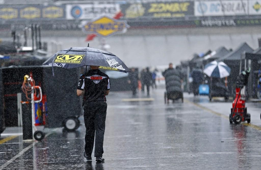 A man walks through the pit area as rain falls before a NASCAR Cup Series auto race, Saturday, Aug. 18, 2018, in Bristol, Tenn. (AP Photo/Wade Payne)