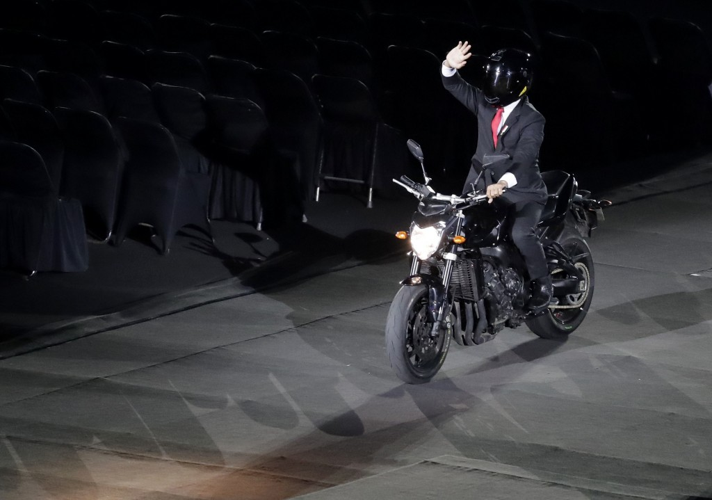 Indonesian President Joko Widodo waves as he arrives on a motorbike to the opening ceremony for the 18th Asian Games in the Gelora Bung Karno Stadium,...