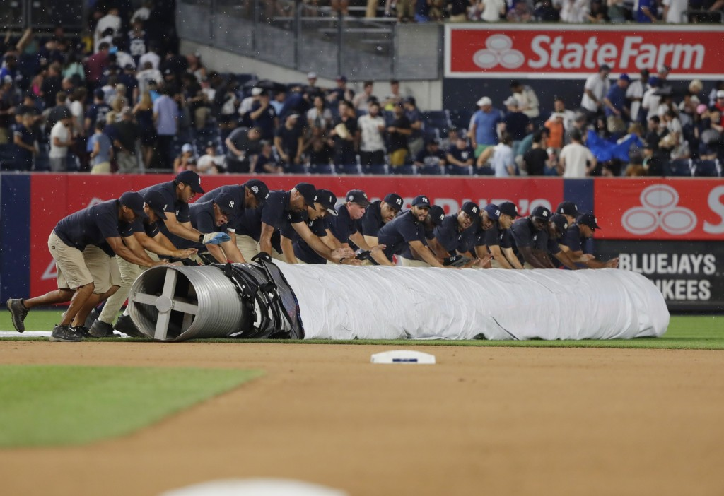 Grounds crew members cover the field during a rain delay in the seventh inning of a baseball game between the New York Yankees and the Toronto Blue Ja...
