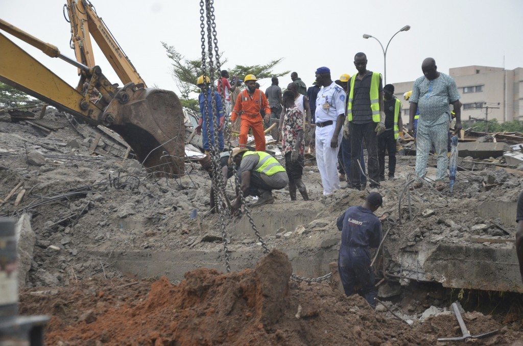 Rescue workers search for people who may be trapped under the rubble of a collapsed under construction building in Abuja, Nigeria, Friday, Aug. 17, 20...