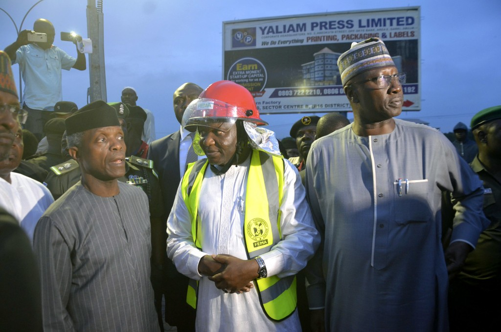 Nigeria's acting President Yemi Osinbajo, left, visits the site of a collapsed under construction building in Abuja, Nigeria, Friday, Aug 17, 2018. Ni...