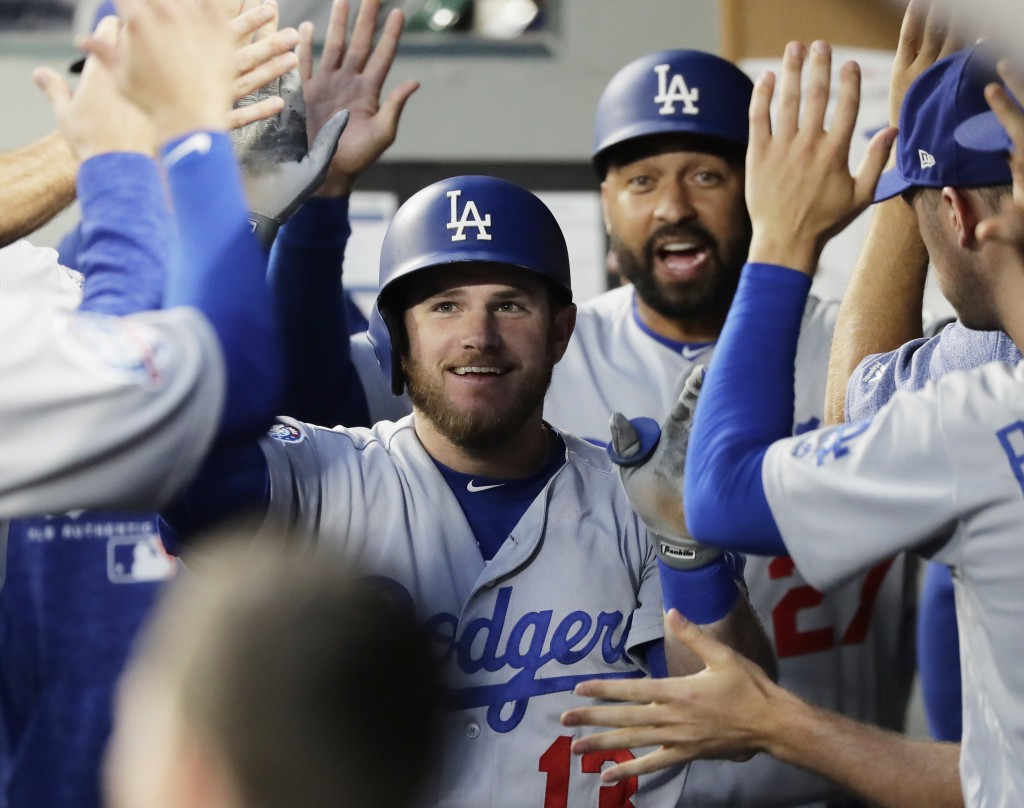 Los Angeles Dodgers' Max Muncy, left, and Matt Kemp, right, after greeted in the dugout after Muncy hit a two-run home run to score Kemp during the fo...